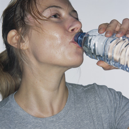 work out sweating woman - how to stay hydrated - why drinking water is important - skincare - health and fitness - handbag.com