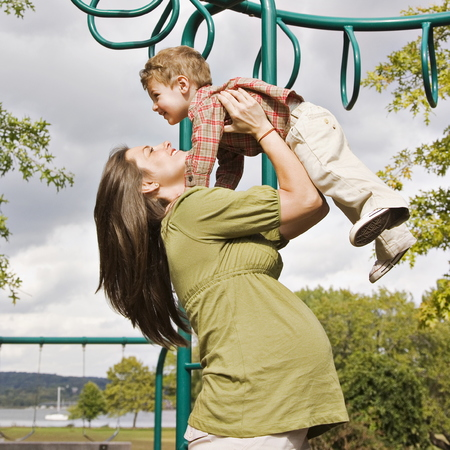 Pregnant woman and child playing in the park