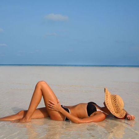 Woman sunbathing on the beach in a bikini