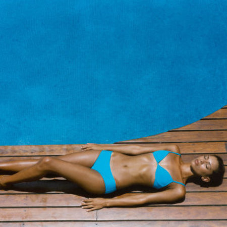 Woman sunbathing by a pool in the sunshine