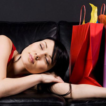 Woman lying on sofa with shopping bags