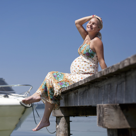 Pregnant lady sitting on a jetty