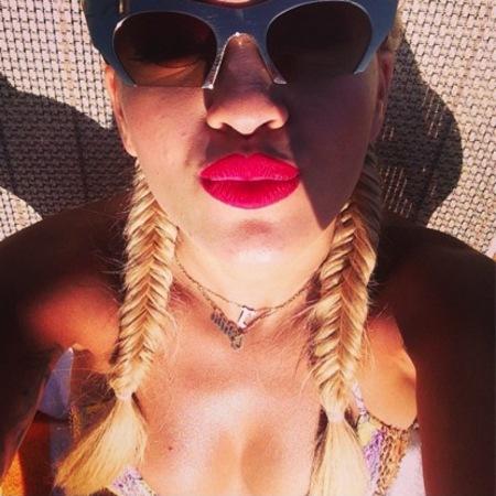 Rita Ora wears red lip and fishtail braids in Malta