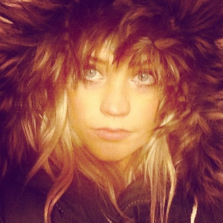 Laura Whitmore with big coat and hood looking like a lion
