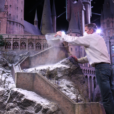 Hogwarts in the snow - warner bros studio - harry potter - christmas days out for adults and children - sieving snow onto model - handbag.com