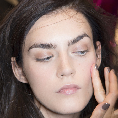model backstage at fashion week - pink blusher - healthy skin - big eyebrows - applying makeup - handbag.com