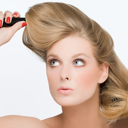 woman using hairbrush - curling hair - volume - red nails - woman doing her hair - handbag.com