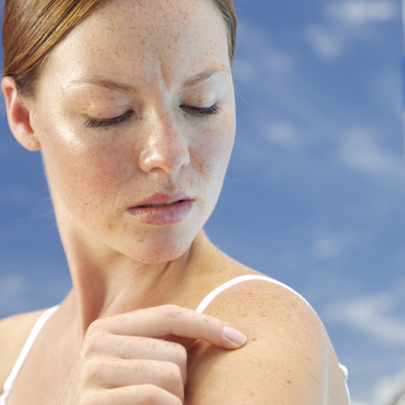 red headed woman - clear skin - looking at arm - mol - melenoma - skin cancer - handbag.com