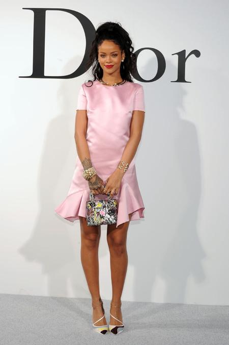 Rihanna - Dior cruise show - demure pink satin dress and lady dior handbag - handbag.com