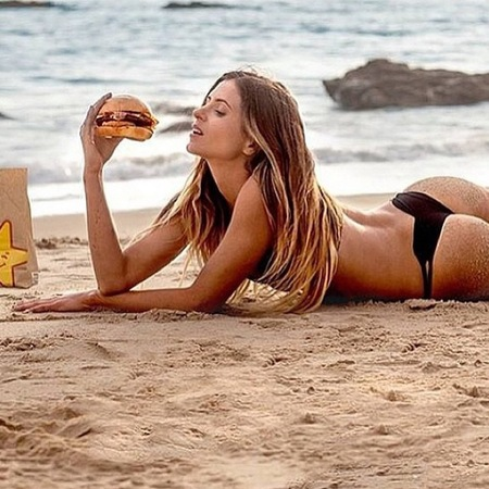You didn't eat that Instagram account - model eating burger on beach - handbag.com