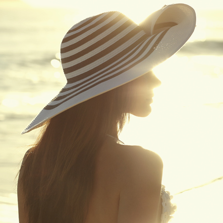 woman-standing on beach-sunset-beach hat-sea-holiday-handbag.com